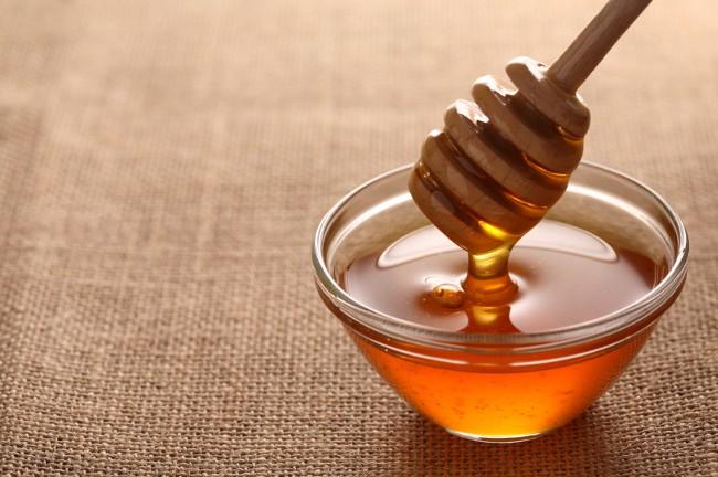 Мед в стеклянной миске с деревянной ложкой