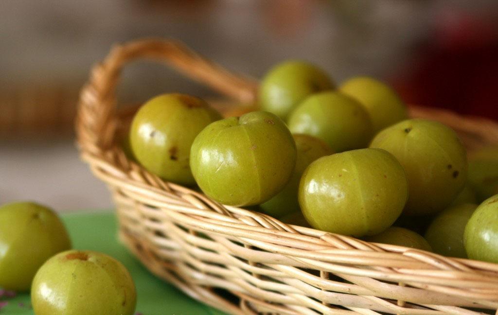 Зеленые ягоды в бежевой плетеной корзине