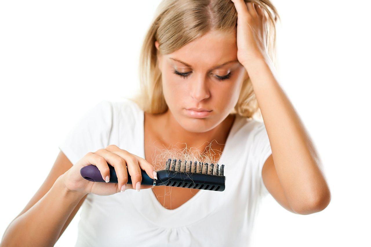 Девушка смотрит на выпавшие волосы