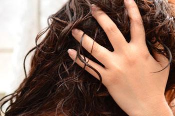 Девушка наносит на волосы питательную маску