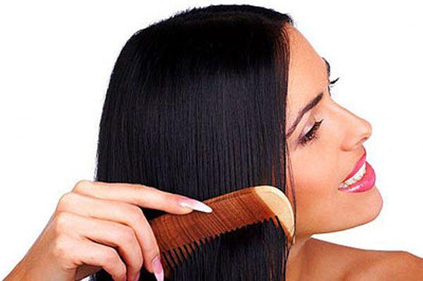 Девушка причесывается деревянной расческой