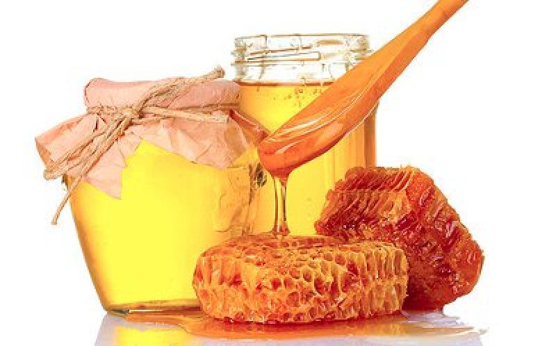 Свежий жидкий мед в банке и соты с деревянной ложкой