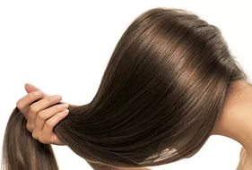 Девушка держит свои длинные, густые русые волосы