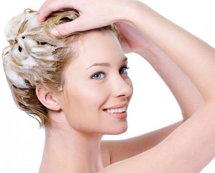 Девушка моет голову с помощью шампуня