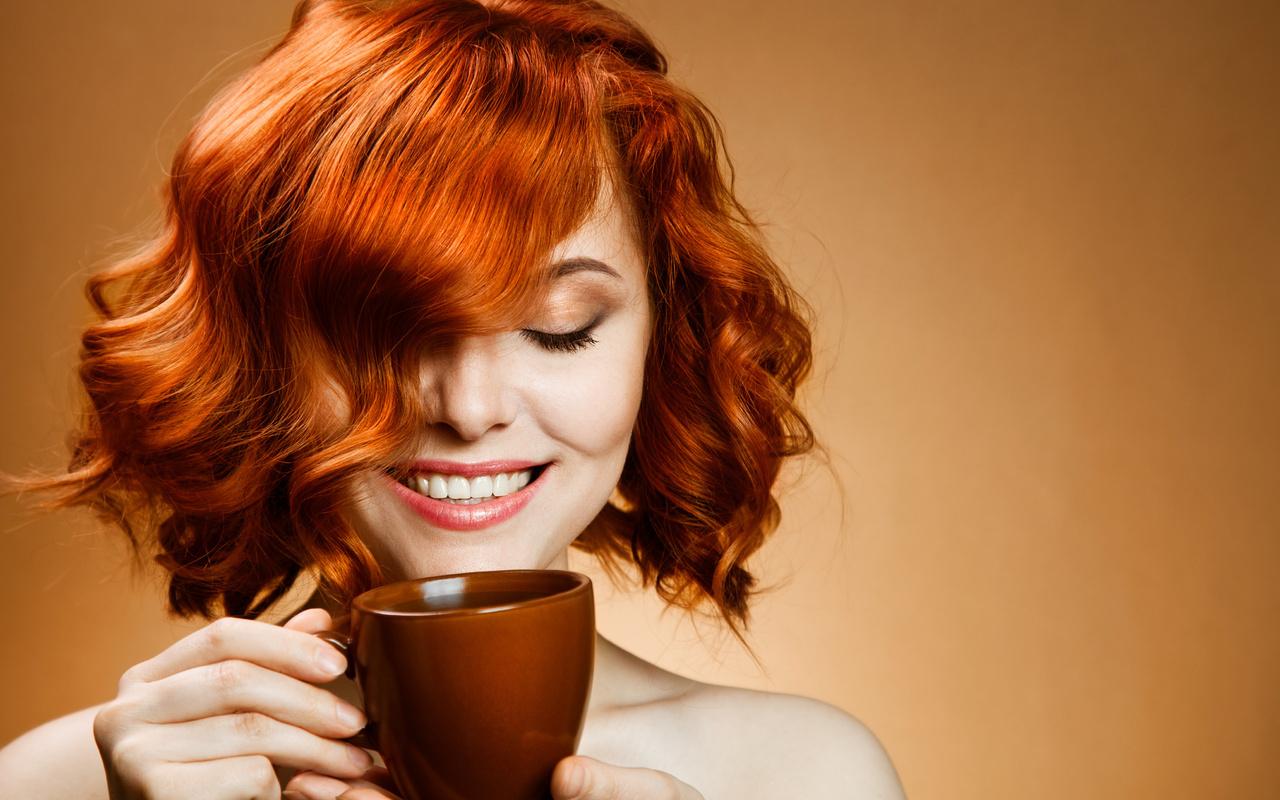 Девушка с рыжими волосами пьет чай