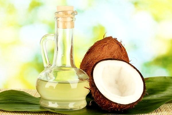 Разрубленный кокос и стеклянная бутылка с маслом