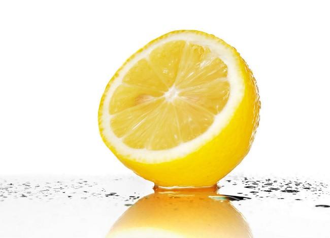 Половина лимона в брызгах сока на зеркальной поверхности