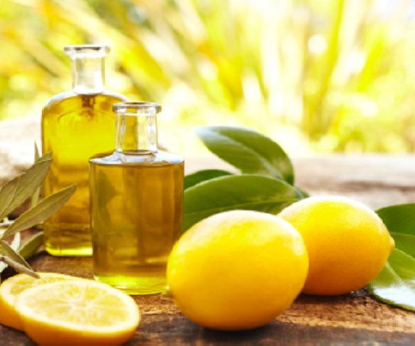 Плоды лимона, листья и масло в стеклянных бутылках