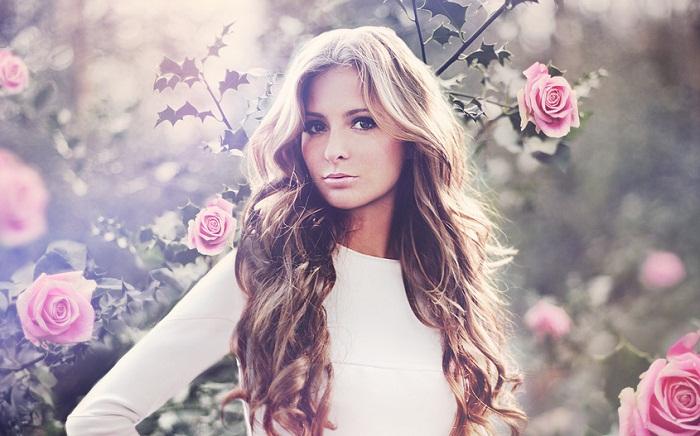 Девушка в белом платье и с красивыми волосами на фоне роз
