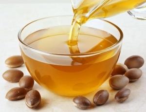 Масло в стеклянной миске и орехи аргании